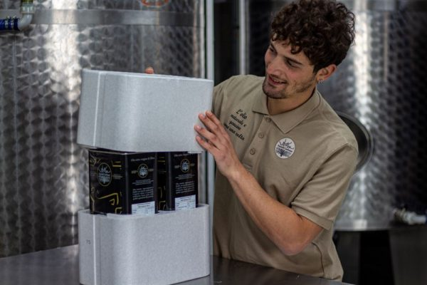 Luca mentre chiude il box contenente le lattine di olio