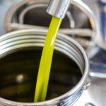 miglior olio italiano | come trovarlo?: degustazione olio | qualità gustative e tattili olio appena spremuto che riempie un recipiente in acciaio