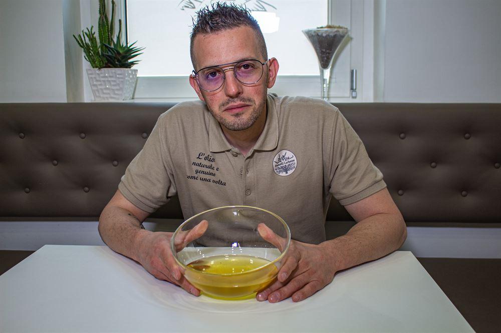 Cos'è l'olio Rancido?   Antonio che ha tra le mani un recipiente contenente olio, con una faccia dubbiosa